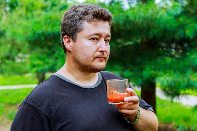 Middle aged man drinks tomato juice on the street Premium Photo