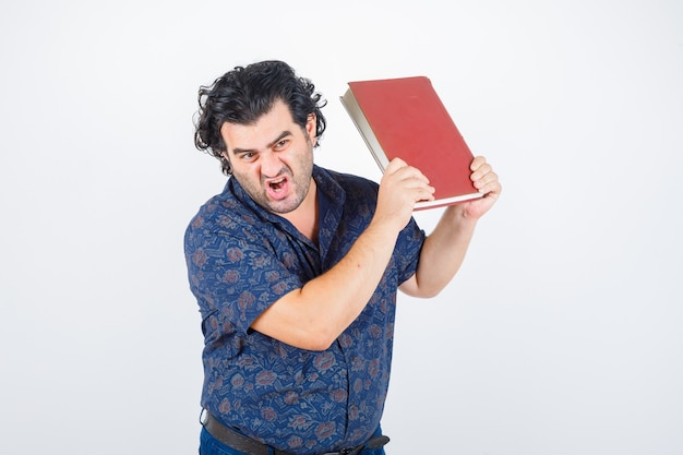 Middle aged man getting ready to throw away book in shirt and looking angry. front view. Free Photo