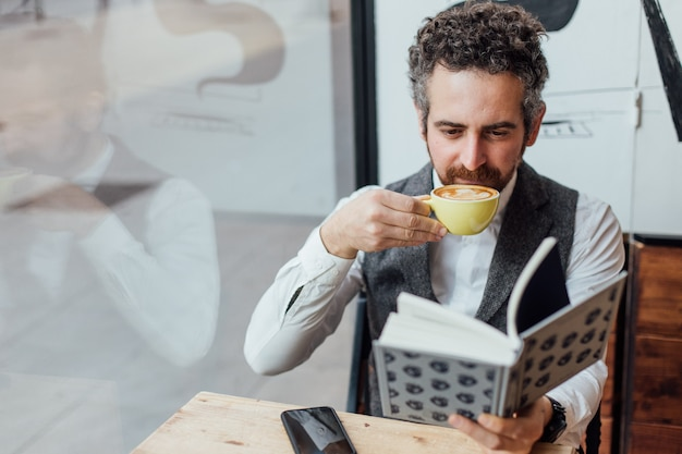 Uomo di mezza età di nazionalità ebraica trascorre il pomeriggio o la mattina in una caffetteria alla moda o hipster Foto Gratuite