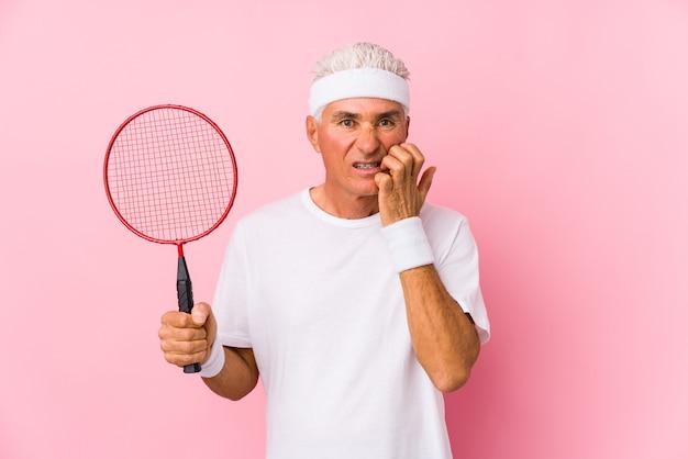 Мужчина средних лет, играющий в бадминтон, кусает ногти, нервничает и очень тревожится. Premium Фотографии