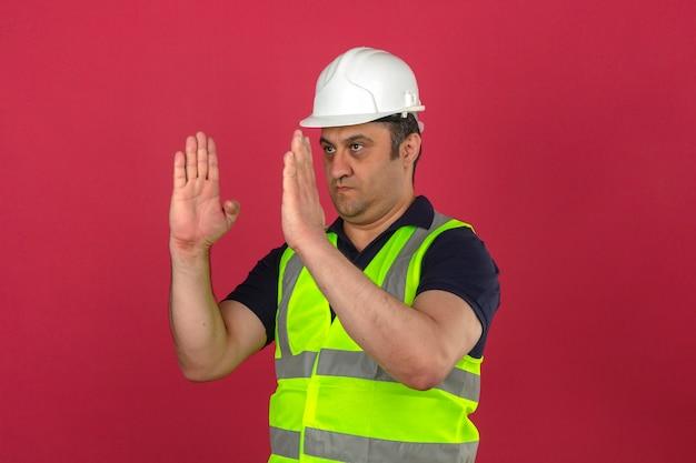 Мужчина средних лет в строительном желтом жилете и защитном шлеме жестикулирует руками, показывая размер над изолированной розовой стеной Бесплатные Фотографии