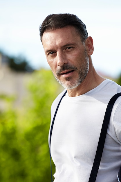 Middle-aged man wearing white shirt with suspenders Free Photo