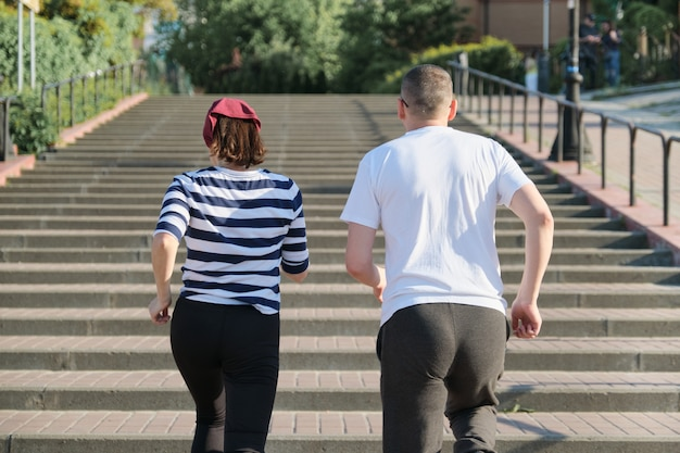 Middle-aged man and woman running upstairs, view from the back. Premium Photo