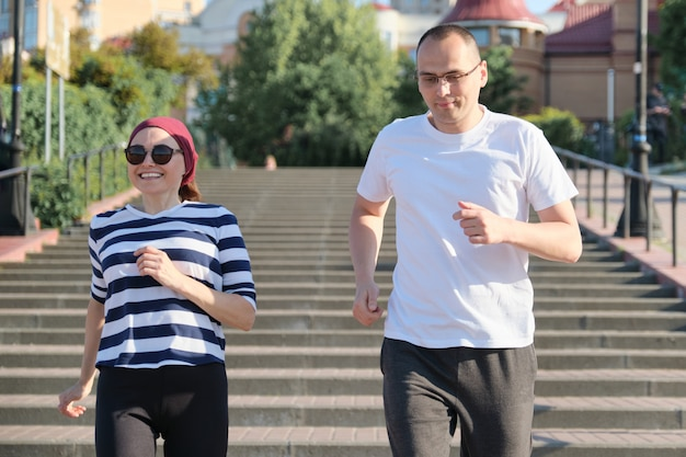 Middle-aged man and woman running upstairs. Premium Photo
