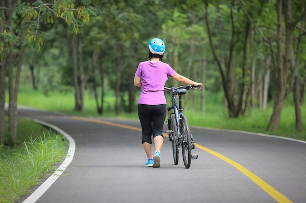 Middle aged relaxing exercise with bicycle in park Premium Photo