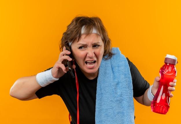 ヘッドバンドと肩にタオルを持った黒のtシャツを着た中年のスポーティな女性が携帯電話で話しているオレンジ色の壁の上に立っている攻撃的な表情で失望した叫びを見て 無料写真