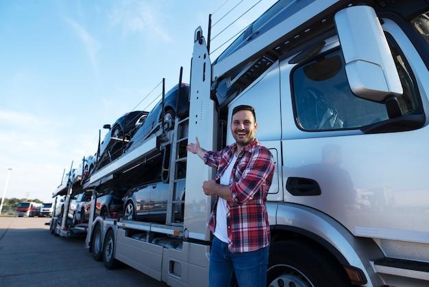 車でトラックトレーラーの前に中年のトラック運転手 無料写真