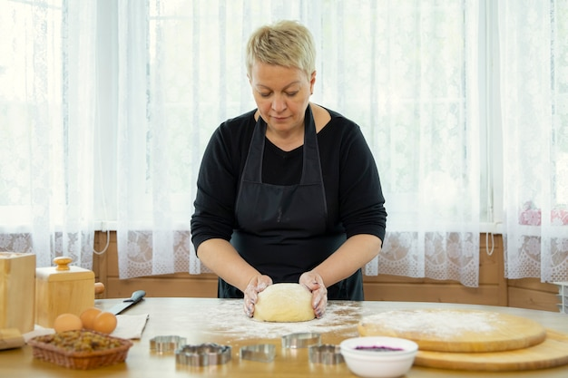 Middle-aged woman in black apron making homemade cookies kneading dough Premium Photo