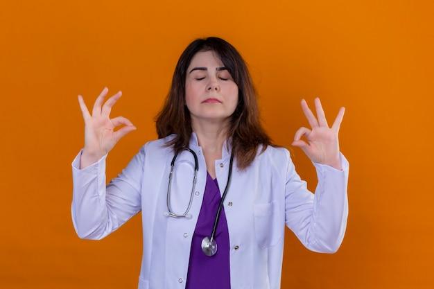 中年の女性医師が白いコートを着て、聴診器でリラックスしてオレンジ色の背景に指で瞑想ジェスチャーをして目を閉じて笑顔 無料写真