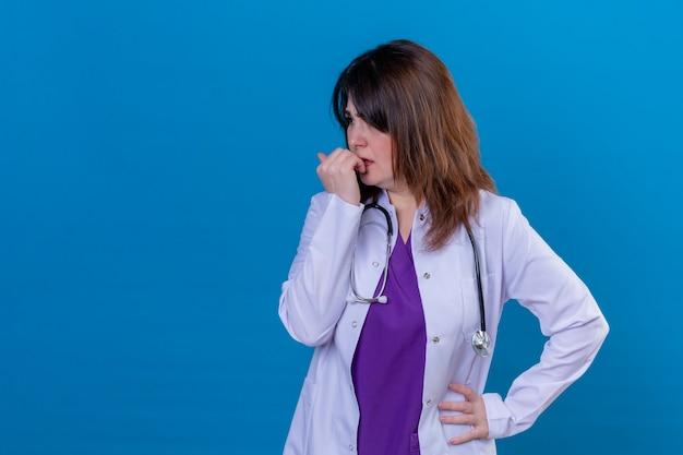 白いコートを着ている中年の女性医師と聴診器を強調し、青い背景の上に立って爪をかむ神経質 無料写真