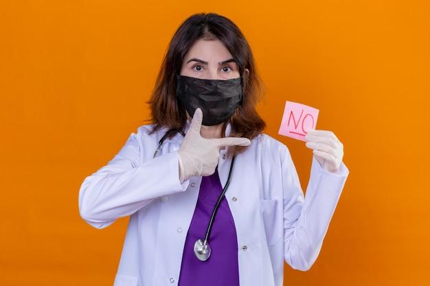 Medico della donna di mezza età che indossa camice bianco nella maschera facciale protettiva nera e con lo stetoscopio che tiene la carta di promemoria senza parola che indica con il dito su sfondo arancione isolato Foto Gratuite