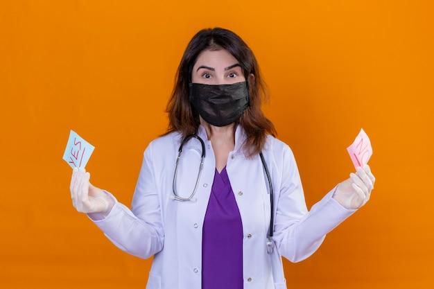 Medico della donna di mezza età che indossa camice bianco nella maschera facciale protettiva nera e con lo stetoscopio che tiene i documenti di promemoria con le parole sì e no guardando la telecamera sorpreso in piedi sopra l'arancio Foto Gratuite