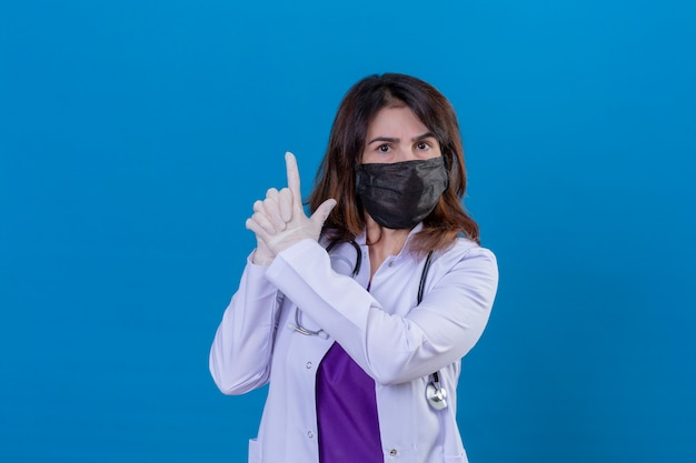 Middle aged woman doctor wearing white coat in black protective facial mask and with stethoscope holding symbolic gun with hand gesture playing killing shooting weapons angry face standing ov Free Photo