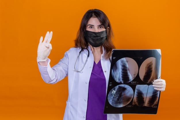 Женщина-врач средних лет в белом халате в черной защитной маске для лица и со стетоскопом, держащим рентгеновский снимок легких, глядя в камеру, делает положительный знак, стоящий на оранжевом фоне Бесплатные Фотографии