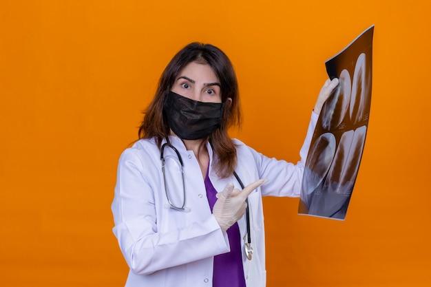 Женщина-врач средних лет в белом халате в черной защитной маске для лица и со стетоскопом, держащим рентгеновский снимок легких, выглядит удивленно, указывая указательным пальцем на рентгеновский снимок, стоя над изолой Бесплатные Фотографии