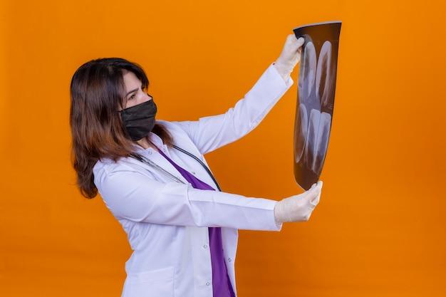 Женщина-врач средних лет в белом халате в черной защитной маске для лица и со стетоскопом, держащим рентгеновский снимок легких, с интересом смотрит на него, стоя на изолированном оранжевом фоне Бесплатные Фотографии
