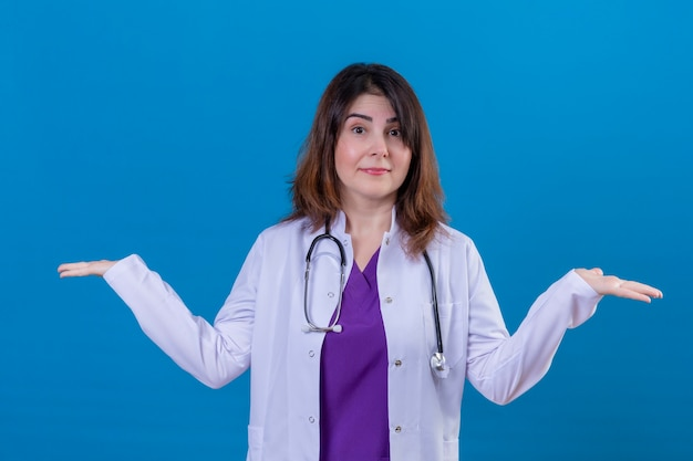 Medico donna di mezza età che indossa camice bianco e con lo stetoscopio all'oscuro e confuso con le braccia aperte nessun concetto di idea in piedi su sfondo blu isolato Foto Gratuite
