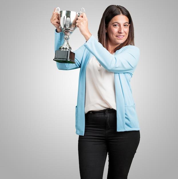 困難な勝利を達成した後にガラスを上げる、興奮と精力的な中年女性 Premium写真