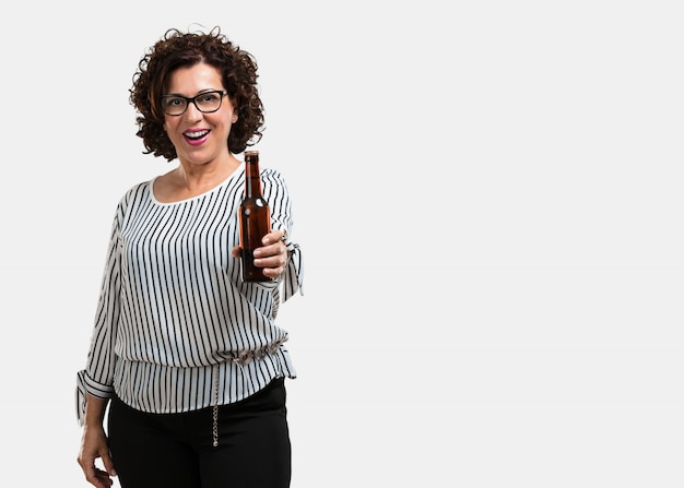 Middle aged woman happy and fun, holding a bottle of beer, feels good after an intense day of work, ready to watch a soccer match on television Premium Photo