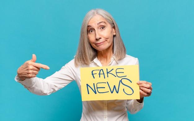 偽のニュースボードを保持している中年女性 Premium写真