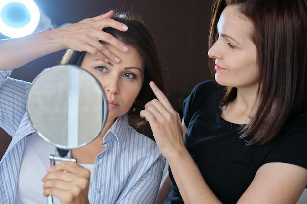 ビューティーサロンで中年の女性、美容師に話して、鏡を見て Premium写真