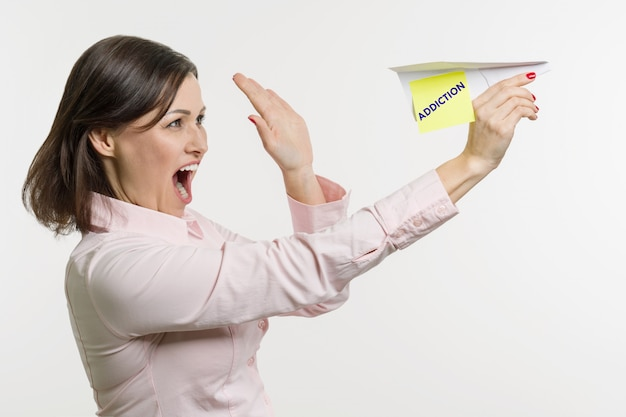 Middle-aged woman lets out paper airplane with word addiction. Premium Photo