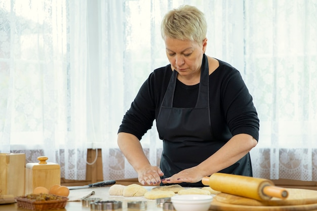 Middle-aged woman making homemade cookies and pastry kneading dough Premium Photo