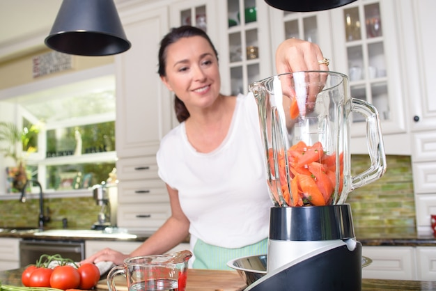 Middle aged woman making smoothie in blender in modern kitchen ...