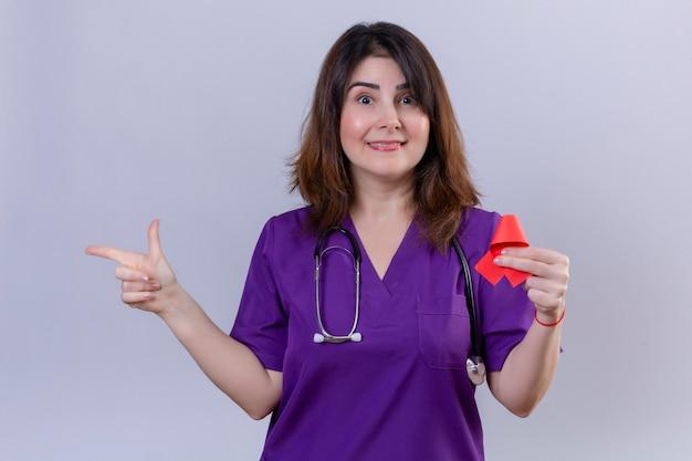 Uniforme d'uso della donna dell'infermiera di mezza età e con lo stetoscopio che tiene nastro rosso un simbolo della lotta contro sorridere degli aiuti Foto Gratuite