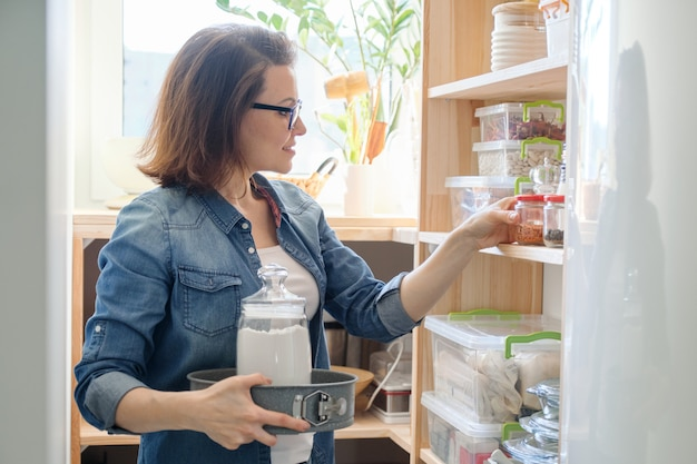 Middle-aged woman picking food from storage cabinet in kitchen Premium Photo
