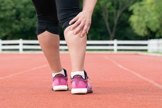 야외 훈련 중 중간 나이 든된 여자 주자 근육통 프리미엄 사진
