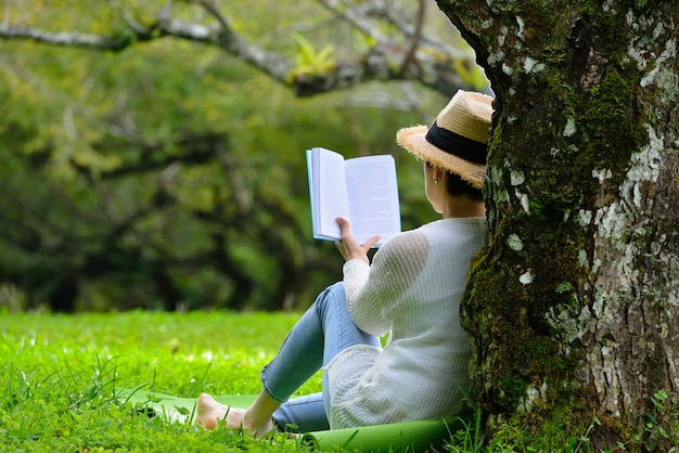 Middle aged woman sitting under a tree reading a book in the park Premium Photo