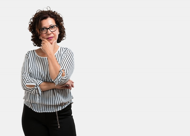 Middle aged woman thinking and looking up, confused about an idea Premium Photo