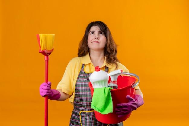 Женщина средних лет в фартуке и резиновых перчатках держит ведро с инструментами для уборки и шваброй, глядя вверх с задумчивым выражением лица, думая, что сомневаясь, стоит над оранжевой стеной Бесплатные Фотографии