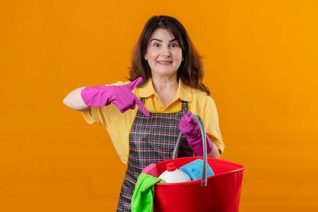 オレンジ色の壁3の上にポジティブで幸せな立っている笑顔を指して指しているクリーニングツールでバケツを保持しているエプロンとゴム手袋を身に着けている中年の女性 無料写真