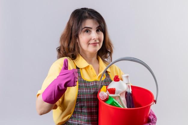 Женщина средних лет в фартуке и резиновых перчатках держит ведро с чистящими средствами Бесплатные Фотографии