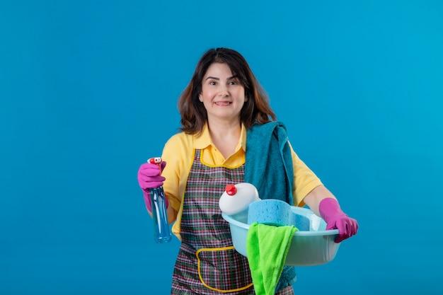中年の女性がエプロンとゴム手袋をはめて、クリーニングスプレーと洗面器を保持しているクリーニングツール 無料写真
