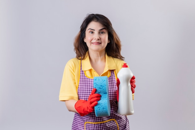 クリーニングスプレーとスポンジを保持しているエプロンとゴム手袋を着用して中年の女性 無料写真