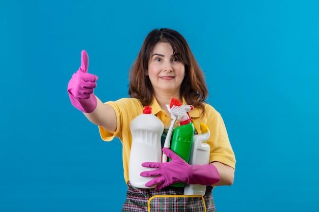 Женщина средних лет в фартуке и резиновых перчатках держит чистящие средства Бесплатные Фотографии