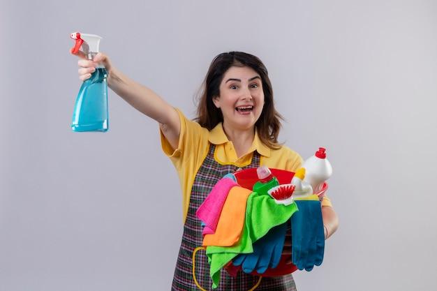 中年の女性が掃除道具とバケツを保持しているエプロンを身に着けている笑顔のスプレーを元気よく終了し、白い壁の上に立って幸せ 無料写真
