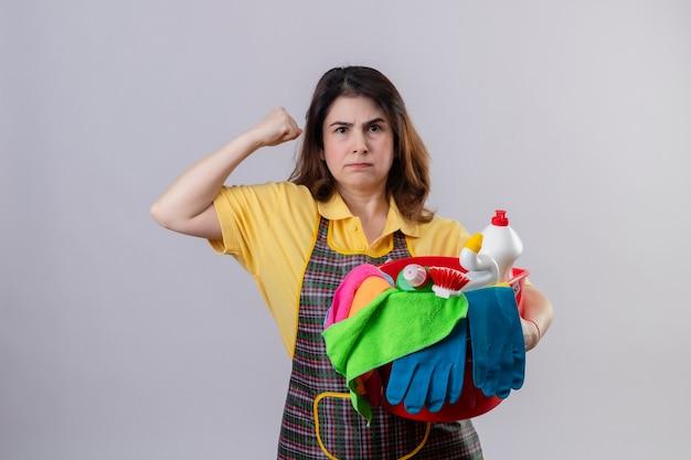 Donna di mezza età che indossa il grembiule che tiene la benna con gli strumenti di pulizia che sembra scontenta del viso accigliato che alza il pugno in piedi sopra il muro bianco Foto Gratuite