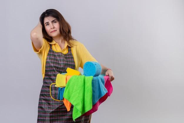 Donna di mezza età che indossa il grembiule che tiene la benna con strumenti di pulizia che sembrano stanchi e sovraccarichi di lavoro in piedi sul muro bianco Foto Gratuite