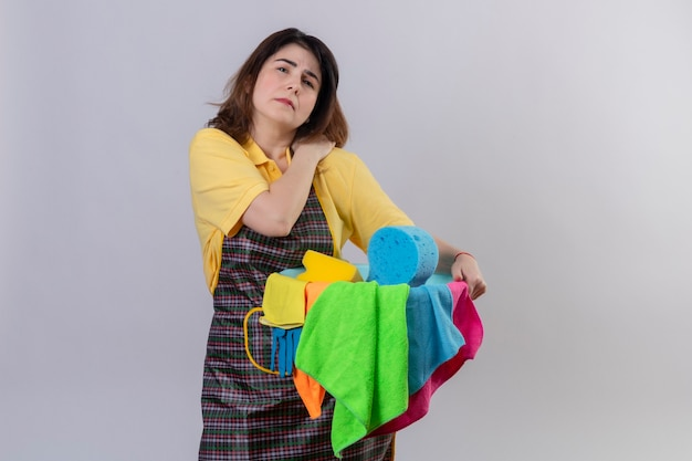 Middle aged woman wearing apron holding bucket with cleaning tools looking unwell touching her shoulder having pain standing over white wall Free Photo