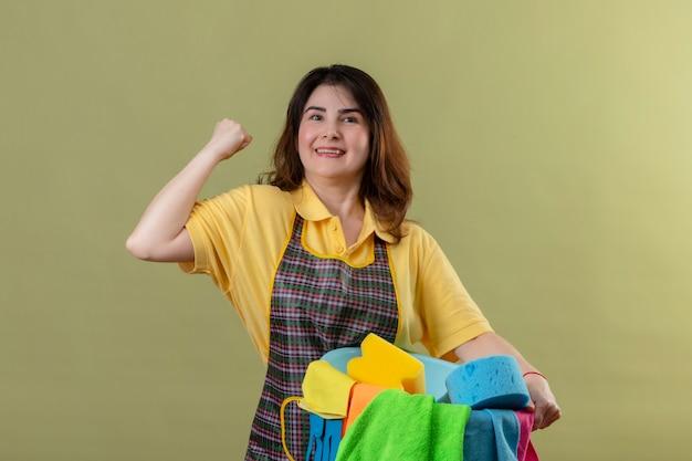 Donna di mezza età che indossa un grembiule tenendo la benna con strumenti di pulizia alzando il pugno rallegrandosi del suo successo sorridendo allegramente guardando fiducioso in piedi oltre il muro verde Foto Gratuite