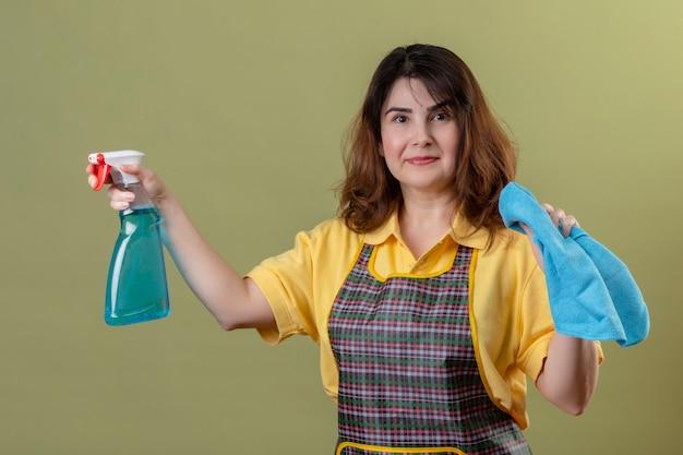 Donna di mezza età che indossa un grembiule azienda spray per la pulizia e tappeto sorridente positivo e felice in piedi oltre la parete verde Foto Gratuite