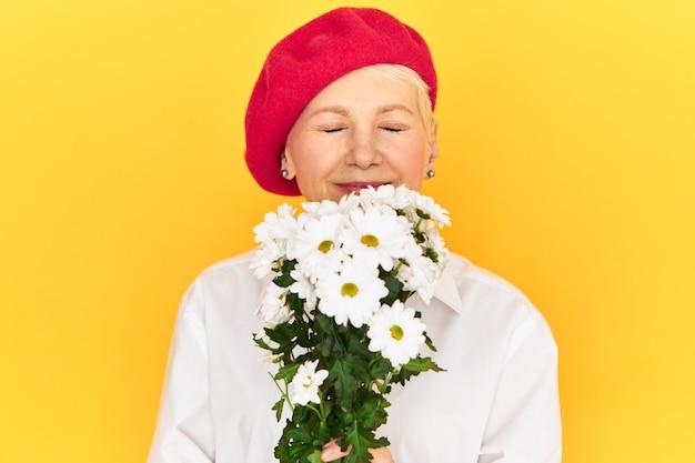 그녀의 생일에 주어진 흰 민들레 꽃의 꽃다발을 들고 우아한 붉은 보닛을 입은 중간 나이 든 여자, 행복한 즐거운 표정, 기쁨으로 눈을 감고, 신선한 꽃 향기를 흡입 무료 사진