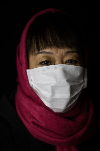 Donna di mezza età con un hijab marrone che indossa una maschera Foto Gratuite