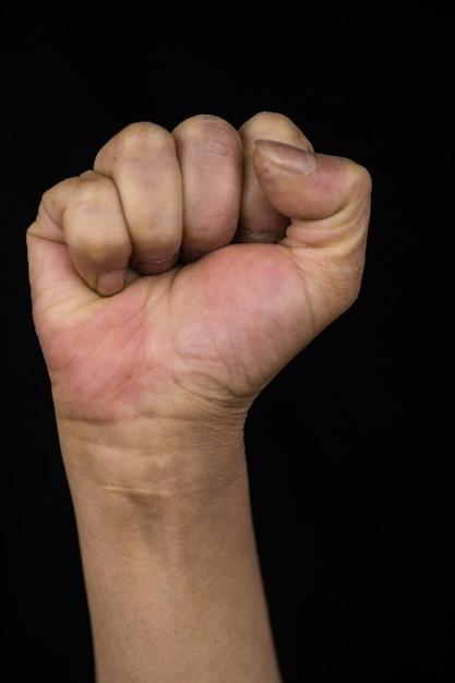 Женщина средних лет с вытянутой рукой показывает кулак, демонстрируя права и возможности женщин Бесплатные Фотографии