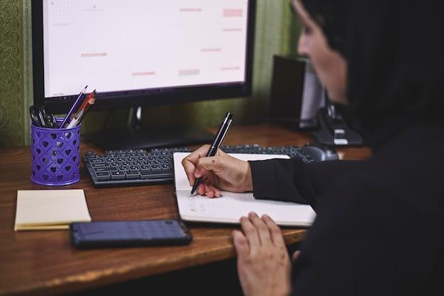 Middle eastern female entrepreneur. busy arabian businesswoman. woman in traditional arabian clothing hijab or abaya working on pc Premium Photo