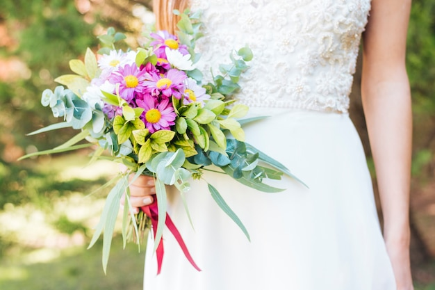 Midsection of a bride's hand holding flower bouquet Free Photo